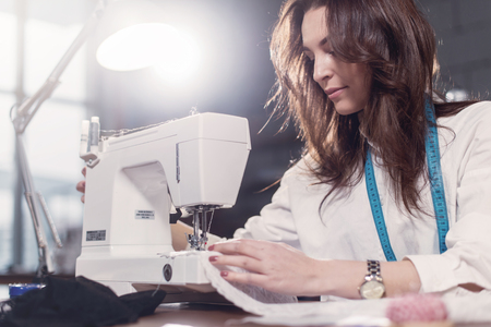 Young female fashion designer working on sewing machine in a workshop