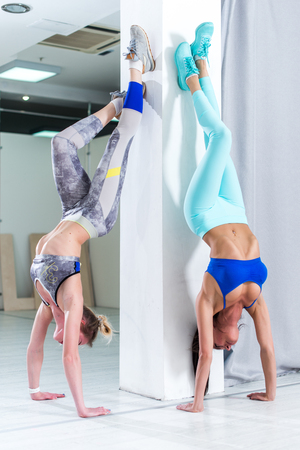 Two fit young Caucasian girls wearing sportswear performing handstand against wall indoors Stock Photo