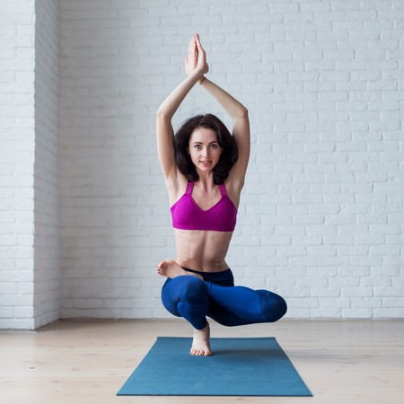 Cute skinny young woman doing toe stand balance posture Padangustasana during yoga session Stock Photo