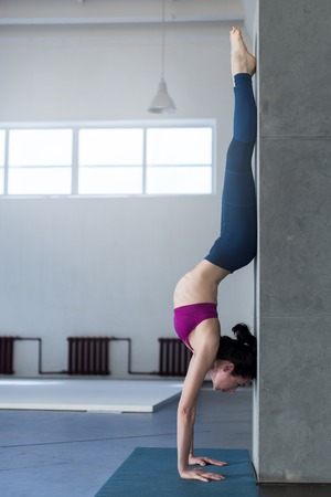 Yoga girl doing handstand with backbend exercise in gym