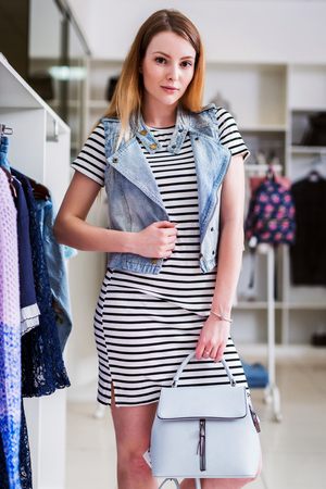 Girl wearing striped dress, denim vest and handbag from summer collection in a fashion boutique