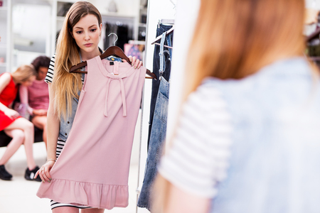 Young woman choosing new pink dress in a fashion boutique