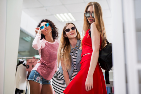 Low-angle shot of stylish glamorous girlfriends choosing new clothes and sunglasses standing posing in front of the mirror in showroom