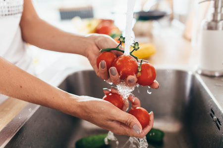 Woman washing tomatoes in kitchen sink close up. Foto de archivo