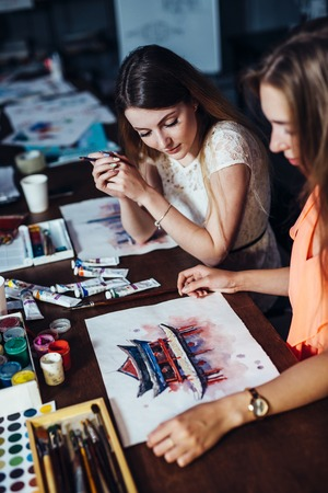 Two young women attending aquarelle painting classes for adults at art school. A girl showing her artwork to friend.