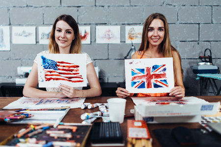 Two smiling female designers of prints showing their works, American and British flags drawn with watercolor technique, sitting at their work desk in creative office Imagens