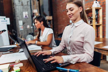 Friendly female office workers wearing formal workwear typing on laptop keyboard working in creative agency Imagens