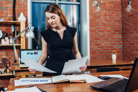 Serious woman reading papers studying resumes standing at work desk in stylish office Imagens