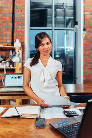 Serious female woman holding documents standing at her workplace in contemporary office Stock Photo