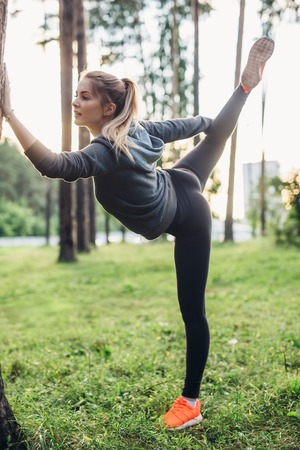 Young sportswoman doing warm-up balance exercise standing on one legs stretching leg and back outdoors
