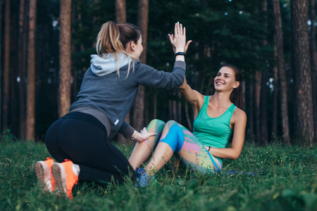 Young female athlete working out with a coach doing crunches giving high-five