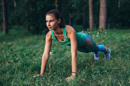 Fit young woman doing push-up exercise on grass in forest