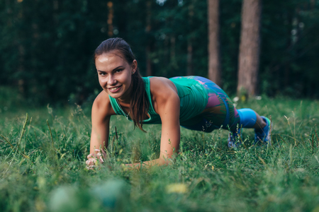 Pretty sporty young female athlete doing planking exercise smiling, looking at camera, working out outdoors