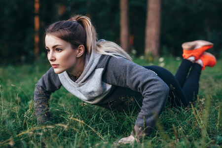 Young pretty blonde working out on grass in park doing knee push-ups Imagens