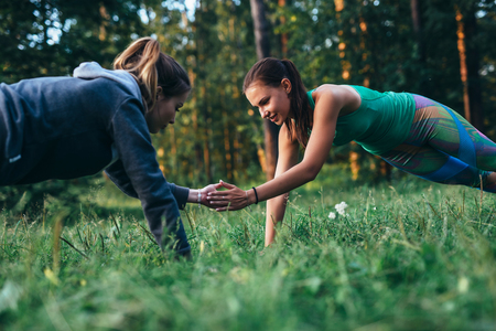 Two girls doing buddy workout outdoors performing push-ups to clap on grass