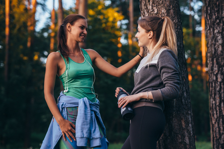 Two female runners relaxing after workout standing near the tree talking in park