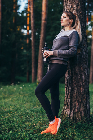Portrait of pretty fit sportswoman wearing tracksuit leaning against tree listening to music in earphones holding sports water bottle standing in forest