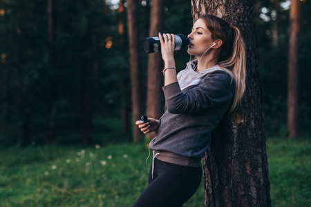 Female jogger recovering after intensive workout standing near the tree drinking water, wearing headphones in park