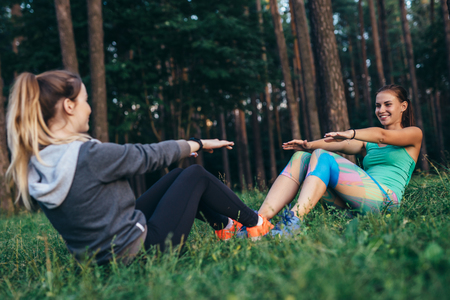 Two smiling sportswomen training outdoors doing full sit-ups sitting opposite each other on grass in forest