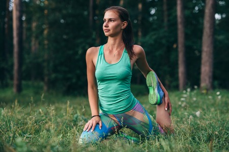 Young sportswoman warming-up before workout doing stretching exercises sitting on grass in park Imagens