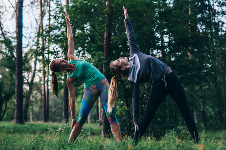 Female friends practicing yoga outdoors doing standing side bend or triangle pose in park