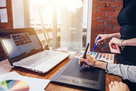 Close-up image of women drawing a project using a graphic tablet and a laptop sitting in modern office Stock Photo