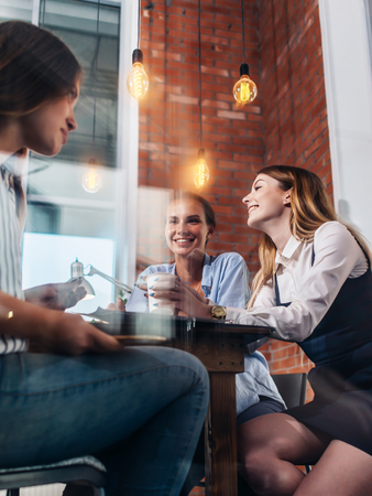 Three happy women drinking coffee, chatting and gossiping in office