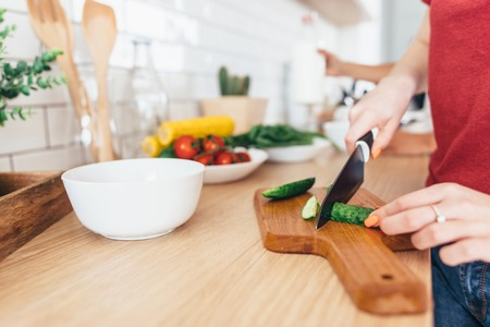 Woman cutting cucumber on the wooden board.