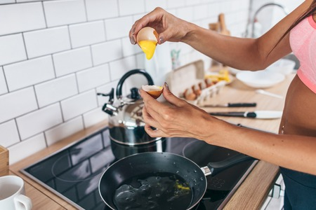 Fit woman in kitchen cracking egg into frying pan. Foto de archivo - 94575724