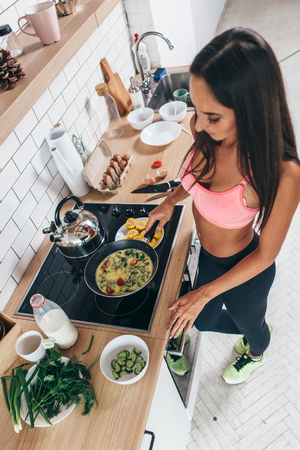Fit woman preparing low carb meal in the kitchen Top view Foto de archivo - 94575726