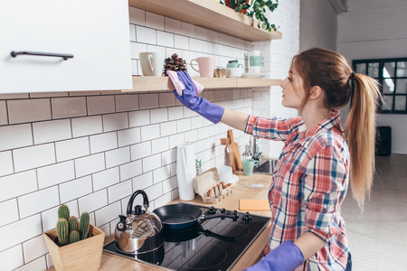 Woman in rubber gloves cleaning kitchen cabinet