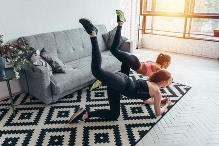 Two sportive female friends doing butt toning exercise performing donkey kicks at home Banco de Imagens