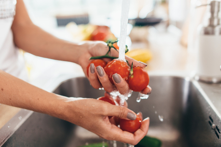 Woman washing tomatoes in kitchen sink close up. Stock Photo