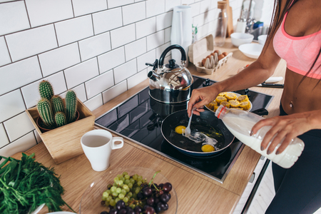 Fitness woman prepare omlette at the kitchen. Pouring milk into frying pan Foto de archivo - 96201787