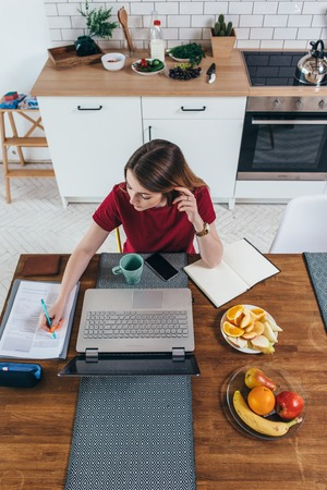 Young woman working with documents and laptop in the kitchen at home. Stock Photo