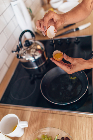 Fit woman in kitchen cracking egg into frying pan Foto de archivo - 96201857