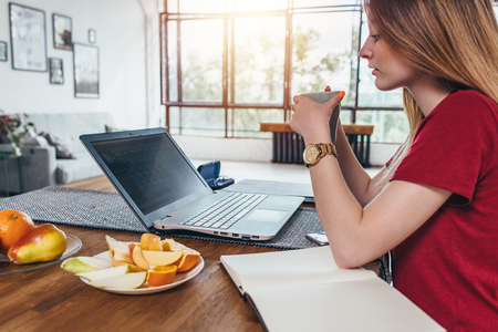 Woman working with laptop eating breakfast drinking coffee Stock Photo