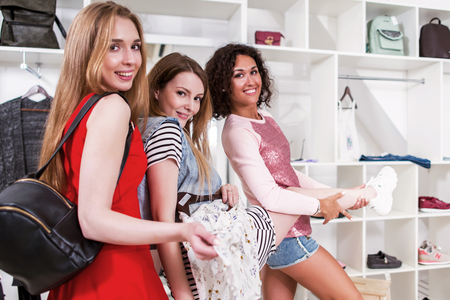 Cool stylish girls having fun standing in funny pose expressing true positive emotions in trendy clothing shop with racks of accessories and clothes in background Stock fotó