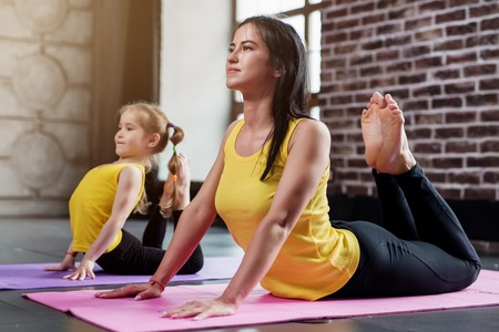 Young mother and her daughter wearing the same sportswear doing king cobra pose during group yoga training