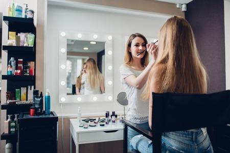 Smiling female esthetician applying makeup using brush to the female model in stylish beauty studio 写真素材