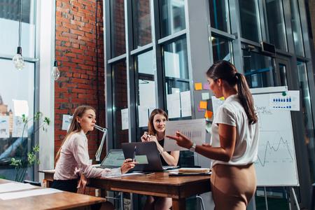 프레젠테이션에서 젊은 경제인. 새로운 사업 전략을 설명하는 다이어그램을 보여주는 여성 동료