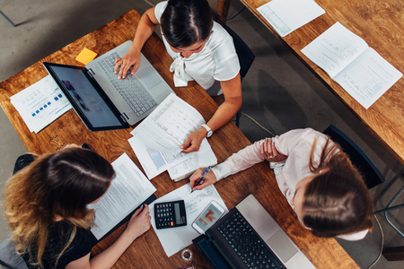 Team of female accountants preparing annual financial report working with papers using laptops sitting at desk in office