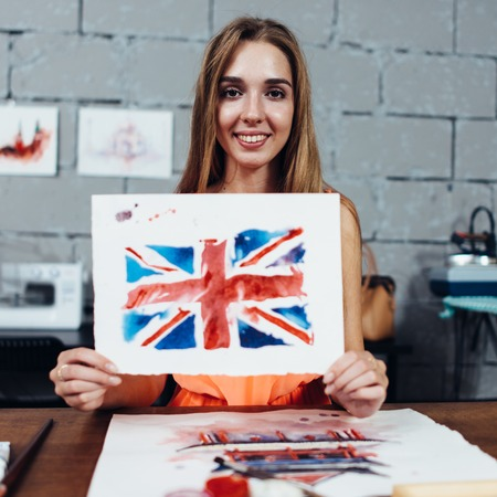 Smiling female artist showing her works, British flag drawn with watercolor technique Фото со стока