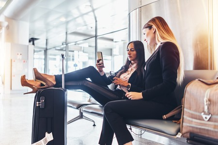 Two successful women resting in arrival hall waiting for a transfer sitting with their legs on suitcase surfing the internet using mobile phone at airport Imagens - 97276884