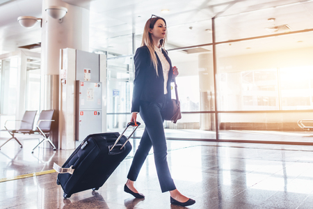 Elegant young woman walking and pulling her suitcase in the airport terminal Stock Photo