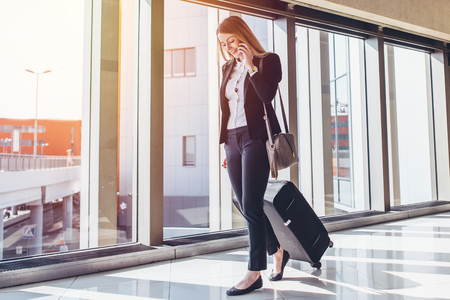 Smiling female passenger proceeding to exit gate pulling suitcase through airport concourse while talking on the phone Stock Photo