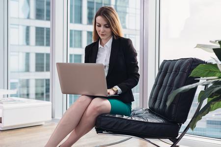 Weiblicher Chefökonom, der Daten unter Verwendung des Laptops sitzt auf Lehnsessel im modernen Büro analysiert Standard-Bild