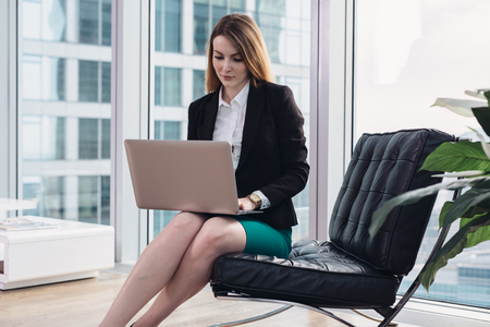 Weiblicher Chefökonom, der Daten unter Verwendung des Laptops sitzt auf Lehnsessel im modernen Büro analysiert Standard-Bild - 97276914