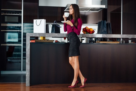 Classy young Latin woman drinking coffee standing in the kitchen relaxing after shopping Imagens
