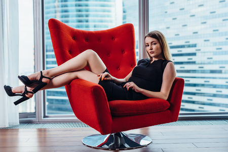 Portrait of sexy businesswoman relaxing in stylish armchair at office Standard-Bild